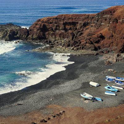 Small boats on a black beach near El Golfo, Lanzarote.