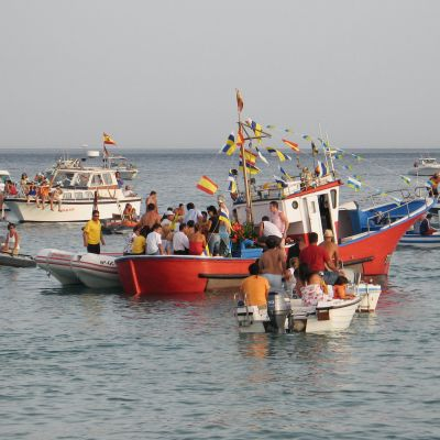 Fishing boats gather to greet the statue of the Virgin during the Fiestas del Carmen in Playa Blanca, Lanzarote.